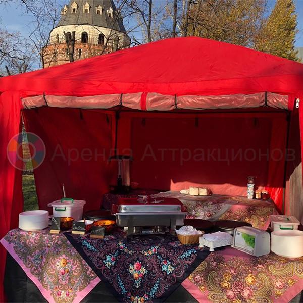 Повар готовит блины в расписной палатке.