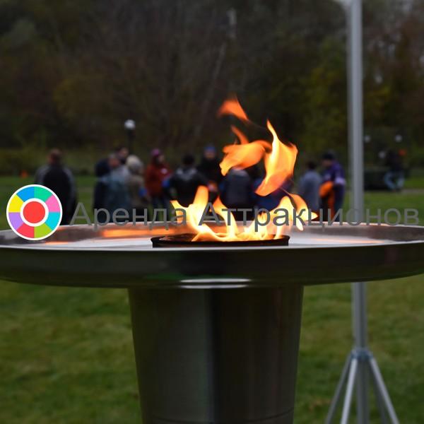 Большой спортивный факел рядом с пьедесталом почета